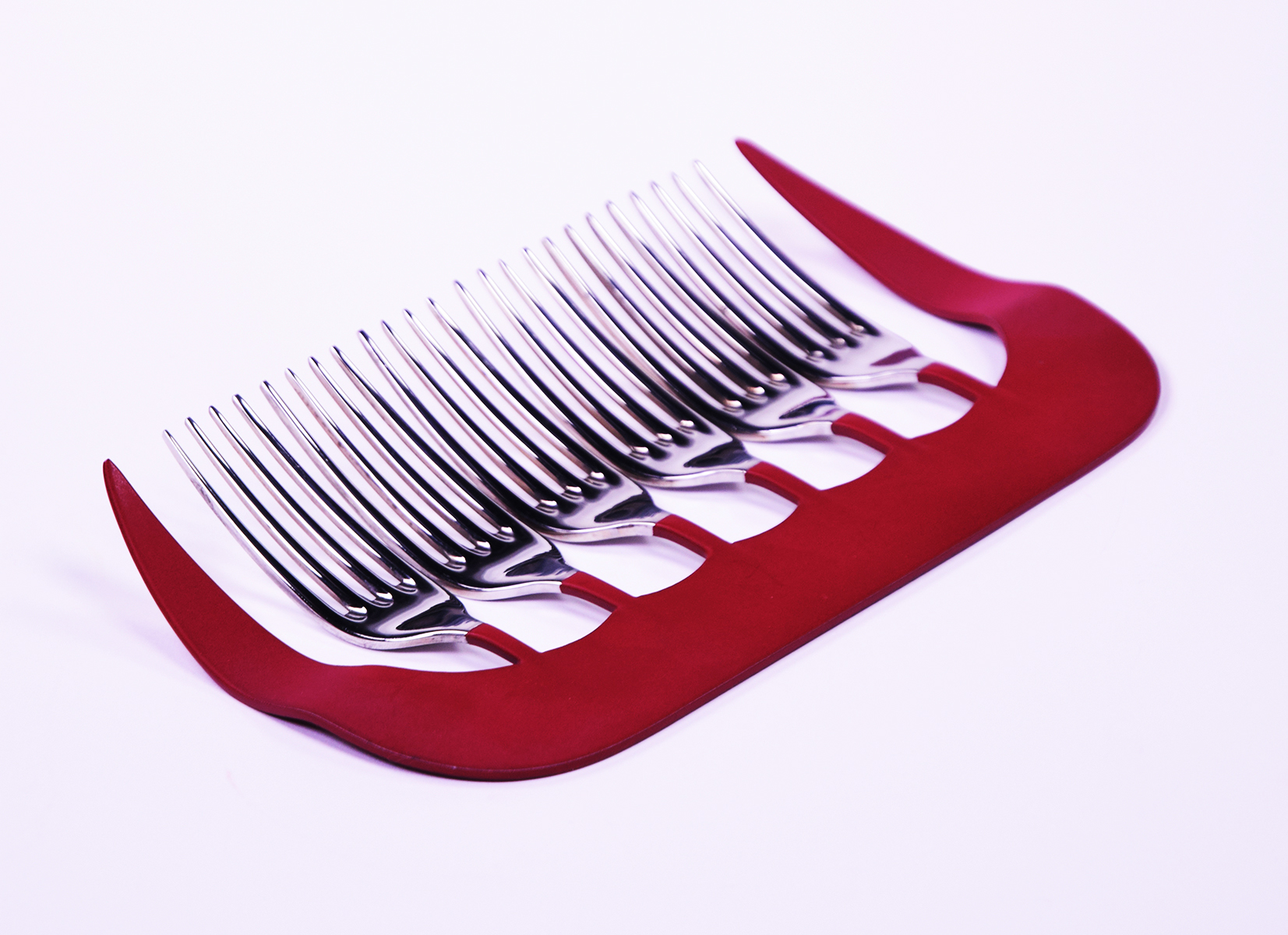 Oversize red metal comb inset with forks, as used for eating